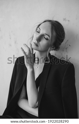 A grayscale shot of an attractive young European female in an elegant black suit posing at the camera with eyes closed and holding hand under chin