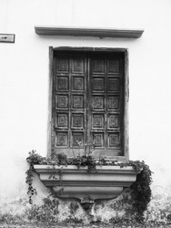 A grayscale shot of ornamented vintage wooden shutters with an outside window sill