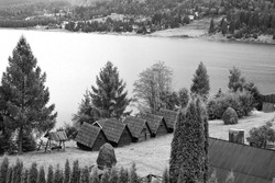 A grayscale shot of the countryside with small wooden houses and a waterscape in the background