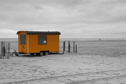 A grayscale shot of the sandy beach with a yellow mobile home on wheels against the gloomy sky