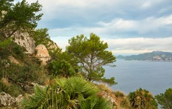 A great hiking trail with ruins of a old bunker. beautiful panoramic view of the cliffs and the coastline during sunrise. turquoise blue water. Spanish island of Mallorca (Majorca).