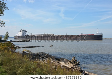 A Great Lakes self-unloading bulk carrier over 700 feet in length leaves the Cleveland Bulk Terminal headed for the open waters of Lake Erie - stock photo