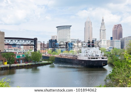 A Great Lakes self unloading bulk carrier ship negotiates a sharp curve in the Cuyahoga River with the downtown Cleveland, Ohio skyline in the background