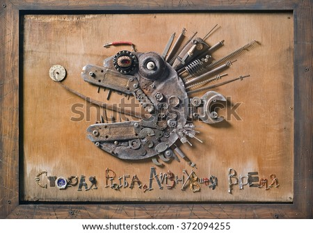 A great recycled art object: the nice fish made from metal trash holding an old clock on its tongue.  stock photo