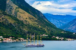 A great sailing ship in the sea against the backdrop of the mountains