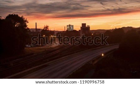A great urban pic of a street and a railway after the sunset. A glowing sky. In the back are any industrial buildings. The sky is mystic and dramatic. Some trees everywhere. A warm, cozy mood.