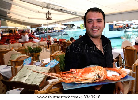 A Greek fish taverna waiter showing off a lobster at a restaurant in Crete, Greece