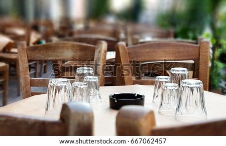 A greek tavern dinning table with paper tablecloth , wooden chairs, transparent inverted glasses and ashtray.