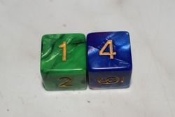 A green and black dice and a blue and purple dice on a white table, showing the numbers 1 and 4