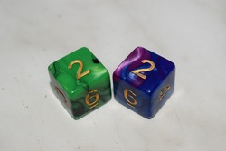 A green and black dice showing the number 2 and a blue and purple dice showing the number 2 on a white table