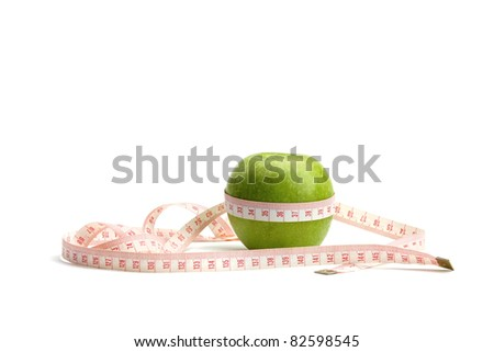 A green apple and a measuring tape - stock photo