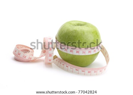 A green apple and a measuring tape, closeup