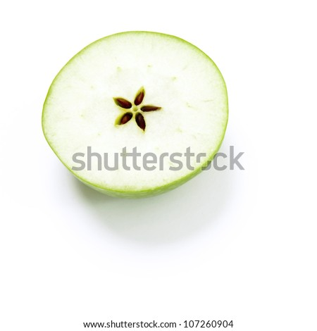 A green apple cut into two halves with a star in the middle.