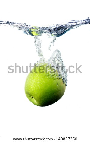 a green apple, falling to the water with the splashing