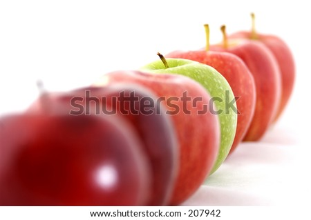 A green apple is the odd one out in a line of red