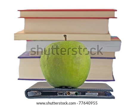 A green apple on an eBook reader, with books in the background - stock photo
