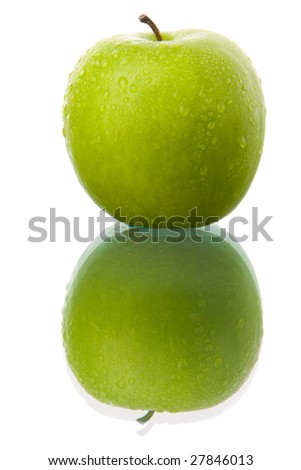 A green apple with much dew around it to enhance its freshness with reflection on glass table