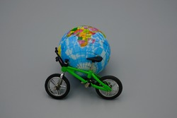 A green bicycle,leaning against a small terrestrial globe. Concept of eco-sustainable mobility