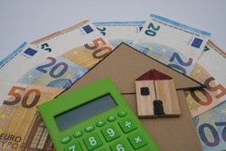 A green calculator, with a wooden house, on top of  a cardboard arrow and some banknotes. Concept of concessions for renovations and building constructions