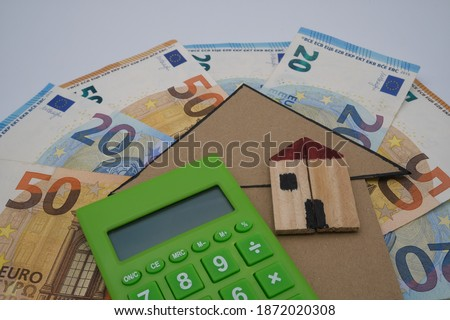 A green calculator, with a wooden house, on top of  a cardboard arrow and some banknotes. Concept of concessions for renovations and building constructions  Сток-фото ©