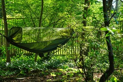 A green camping hammock with bug net used in a backyard