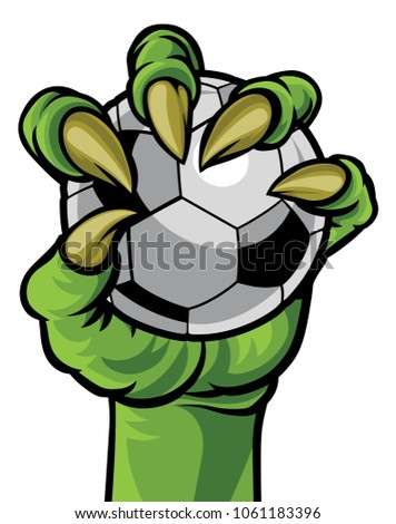A green claw monster hand holding a soccer football ball