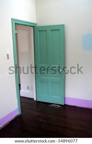 A green door in a room under renovation.