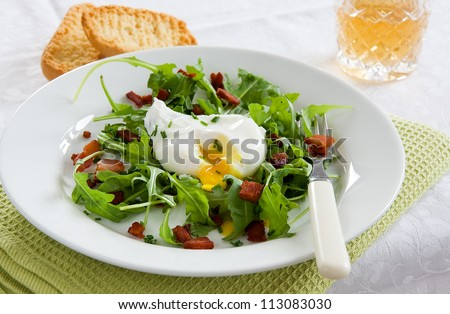 A green French bistro style salad with poached egg and chives on a white plate and table setting
