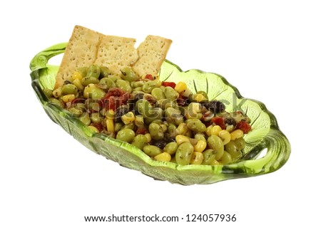 A green glass serving dish with edamame soy bean salad and crackers.