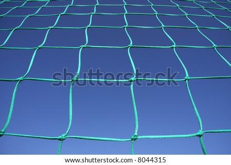A green goal net isolated on a blue sky