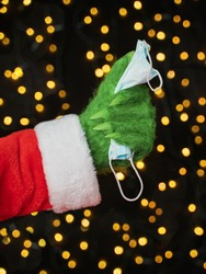 A green hairy hand in a Santa suit clutches a medical mask against the background of Christmas lights