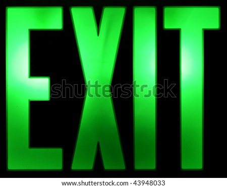 A green illuminated Exit sign isolated on a black background.