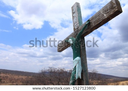 A green image of Jesus Christ nailed on a wooden cross at the top of a sacred hill in a black community in the interior of Brazil at the state of Piauí, drought and poor region