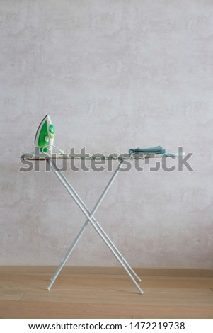 A green iron stands on an ironing board. Ironing. Housework