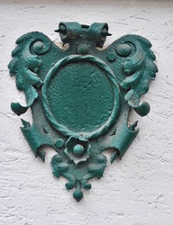 A green, metal heraldry decorated house number plaque, fixed on a wall, without number. Mock up/ template for designers.