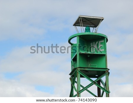 A green navigational buoy with a blue cloudy sky in the background