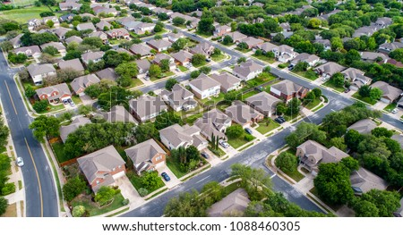 A green neighborhood Suburb houses and homes in new real estate development in Austin , Texas , USA aerial drone view at the corner of the streets