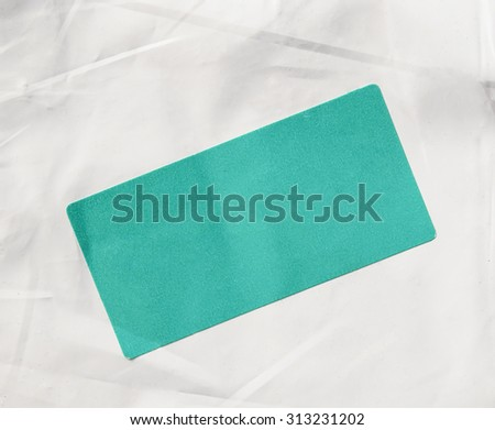 A green paper tag label sticker on a white envelope for mail with copy space