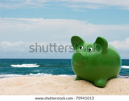 A green piggy bank in the sand at the beach, Vacation Savings - stock photo