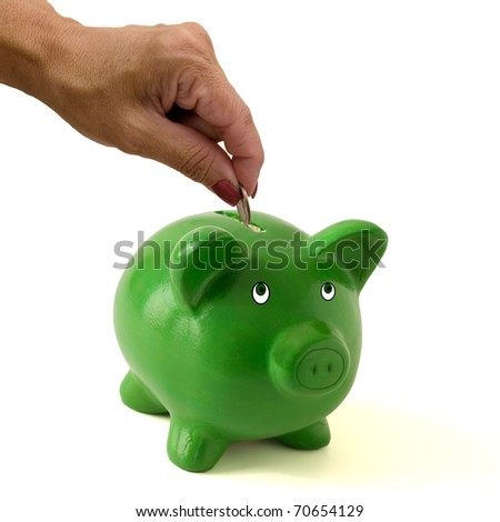 A green piggy bank with a hand putting money in it on a white background, Saving your money