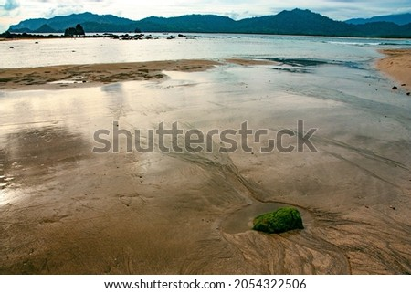 A green rock on clear water of Pulau Merah or Red Island Beach, Banyuwangi, East Java, Indonesia with mountains in the background 商業照片 ©