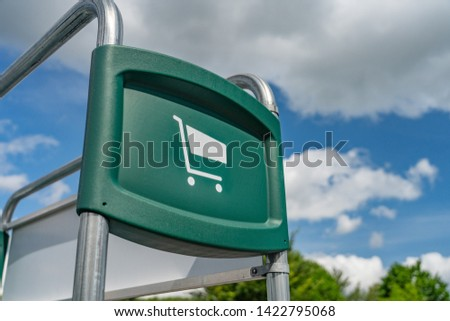 A green sign with a white grocery cart icon showing where to park the carts after use. Blue sky and clouds are blurred in the background. #1422795068