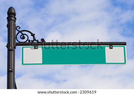 A green street sign on a decorative wrought iron post - stock photo