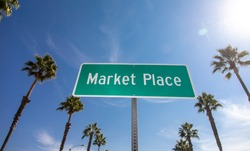 A green street sign that says Marketplace with palm trees and a blue sky background
