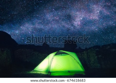 a green tent is illuminated...