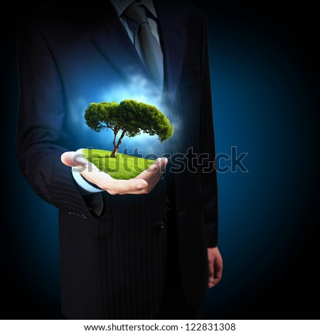 A green tree in the hand of a businessman