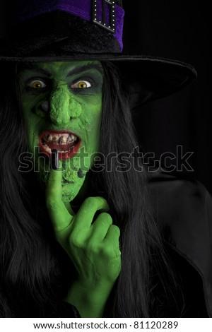 A green wicked witch, dark background.