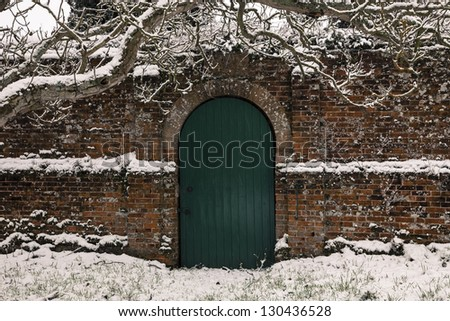 A green wooden door in an old brick wall on a snowy day