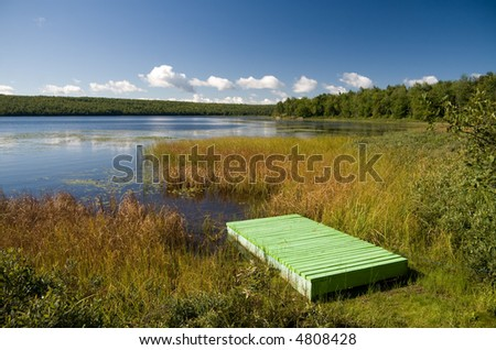 A green wooden pier next to a lake in central Quebec.