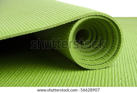 A green yoga/pilates/exercise mat rolled up on white